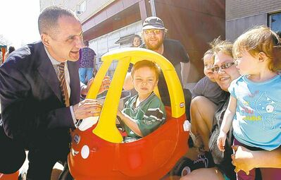 Children and Youth Opportunities Minister Kevin Chief (left) visits Monday with Bernard Pollard and Rachel Thomas and their children Devin (in car), Jessica (right) and Nathan.