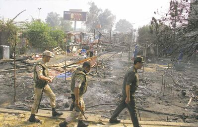 Soldiers walk among smouldering remains of the Muslim Brotherhood protest camp Thursday in the Cairo district of Nasr City.