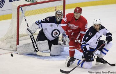 Winnipeg Jets goalie Ondrej Pavelec blocks a shot near Detroit Red Wings left winger Jiri Hudler and Jets defenceman Zach Bogosian in Detroit Saturday.