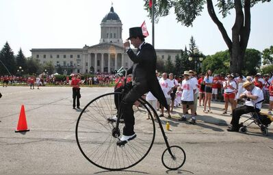 Martin Barnes rides a remake of an 1875 Penny Farthing bicycle during the Living Flag event taking place on the grounds of the Manitoba Legislative Building Monday morning.
