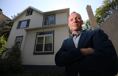 Blair Holm of Kilkenny Real Estate in front of a triplex at 290 River Ave. that will be converted to condos.