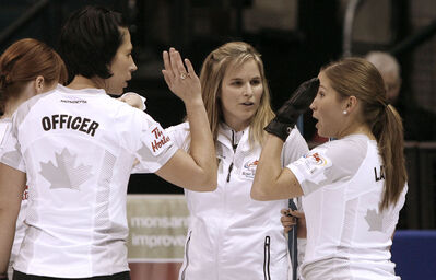 Skip Jennifer Jones and teammates high five each other after winning their game 9-7 in 11 ends against Team Middaugh this morning at the Roar of the Rings at the MTS Centre.