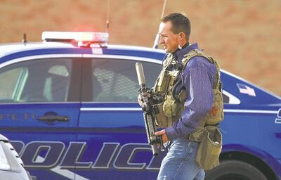 A Natrona County  sheriff's deputy in tactical gear leaves Casper  College Friday  morning after a teacher was killed by a man wielding a sharp-edged weapon. The man later killed himself.