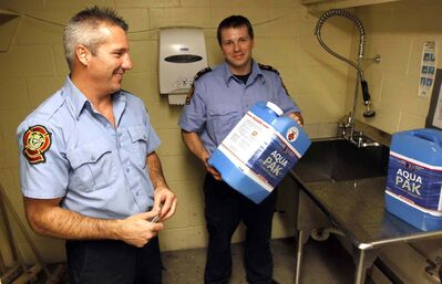 Jay Simons and Dale Worrall of the Winnipeg Fire Paramedic Service with water jugs the WFPS is handing out.