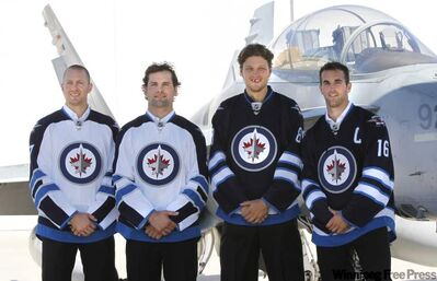 From left, Eric Fehr, Mark Stuart, Nik Antropov and Captain Andrew Ladd at a ceremony at 17 Wing Tuesday where the Winnipeg Jets unveiled their dark home and white away jerseys.