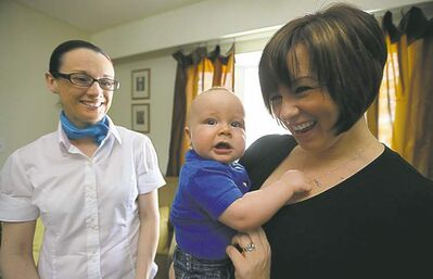TREVOR HAGAN/WINNIPEG FREE PRESS Baby sleep consultant and parenting coach Nichola Mitchell, along with Felicia Wiltshire and her nine-month-old, Mason, Sunday, March 24, 2013.