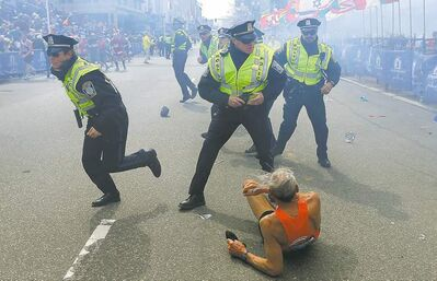John Tlumacki / Boston Globe / The Associated Press Bill Iffrig, 78, from Stevens, Wash., lies on the ground as police officers react to a second explosion at the finish line of the Boston Marathon on Monday.