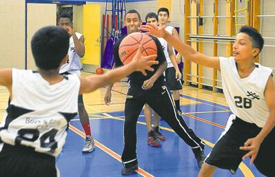 Bisons guard Amir Ali (centre) helps out in the Victor Mager School gym while Boys and Girls Clubs participants Noman Pervez (left) and Salman Ahmed battle for the basketball Thursday.