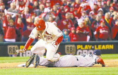 The Cardinals' Allen Craig trips over Red Sox third baseman Will Middlebrooks on Saturday night.