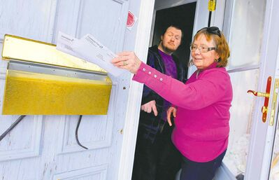 Val Surbey, with her son, Timothy, retrieves letters from their mailbox. That will change this fall when Canada Post stops home delivery in her neighbourhood.