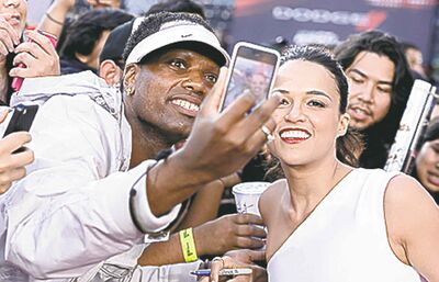"""FILE - This May 21, 2013 file photo shows actress Michelle Rodriguez posing for a photo with a fan at the LA Premiere of the """"Fast & Furious 6"""" at the Gibson Amphitheatre in Universal City, Calif. The practice of freezing and sharing our tiniest slices of life in """"selfies"""" has become so popular that the granddaddy of dictionaries, the Oxford, is monitoring the term as a possible addition. (Photo by Dan Steinberg/Invision/AP, file)"""