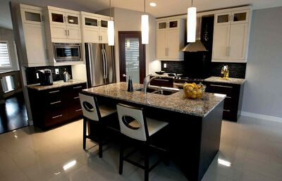 The kitchen features an island with eating nook for two, a corner pantry and extra-wide aisles.
