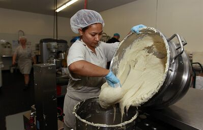 "Bertha Domimguez prepares gluten-free dough at Pure Knead bakery sandwich bread in Decatur, Ga. Scientists suggest that there may be more Celiac disease today because people eat more processed wheat products than in decades past, which use types of wheat that have a higher gluten content. Or it could be due to changes made to wheat, said the Mayo Clinic's Dr. Joseph Murray. In the 1950s, scientists began cross-breeding wheat to make hardier, shorter and better-growing plants. It was the basis of a so-called ""Green Revolution"" that boosted wheat harvests worldwide. (AP Photo/John Bazemore)"