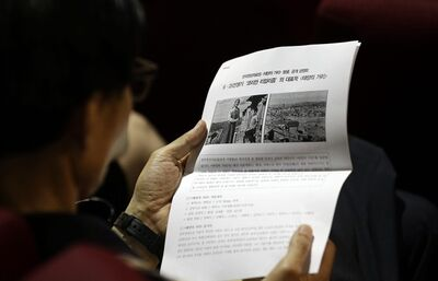 "A South Korean filmgoer looks at the leaflet of South Korean movie ""The Street of the Sun,"" during its first screening in six decades at Korean Film Archive in Seoul, South Korea, Tuesday, June 25, 2013. The only surviving Korean War-era South Korean film by director Min Kyoung-sik, got the screening Tuesday, the 63rd anniversary of the beginning of the war. Now digitally restored, it offers South Koreans a rare glimpse at how their ancestors lived amid the destruction and poverty of war. The movie was the debut feature of Min, a South Korean director who took a camera to the streets of Daegu in 1952, while a stream of refugees poured in. (AP Photo/Lee Jin-man)"