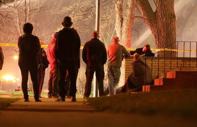 People watch fire from behind police lines.