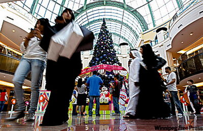 An Emirati couple and other nationalities pass by a giant Christmas tree at a shopping mall in Dubai.
