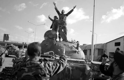 Syrian fighters celebrate the victory on top of a tank they took after storming a military base in Aleppo, Monday, Nov. 19, 2012. (AP Photo/ Khalil Hamra)