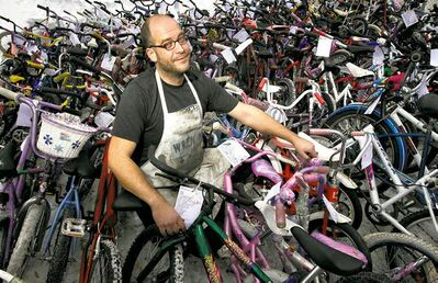 Pat Krawec stands among the finished bikes Sunday during the Cycle of Giving at the Atomic Centre on Logan Avenue.