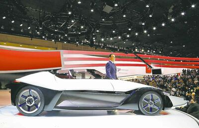 Nissan Motor Co. president Carlos Ghosn with a Nissan BladeGlider concept car.