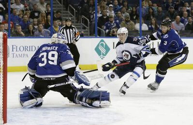 Tampa Bay Lightning goalie Anders Lindback kicks away a shot by Winnipeg Jets centre Mark Scheifele during a game Friday, Feb. 1, 2013, in Tampa, Fla.