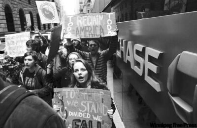 Bebeto Matthews / The ASSOCIATED PressOccupy Wall Street protesters march around One Chase Manhattan Plaza in New York on Oct. 12. The protest, in its fourth week, was launched by the Canadian anti-consumerism group Adbusters.