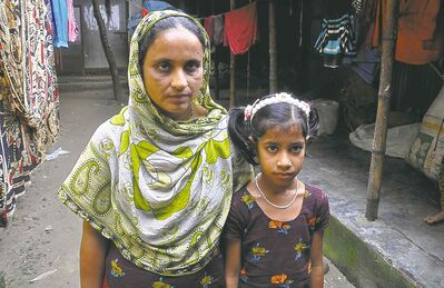 Nazma Akhter, left, and her daughter, Riza, 10, outside their home in a slum in Ashulia, a suburb of Dhaka, Bangladesh. Nazma survived the November 2012 fire in Tazreen Fashions Factory that killed 112 of her co-workers.