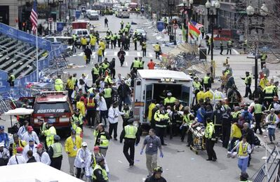 Medical personnel help the injured at the finish line of the Boston Marathon following explosions.
