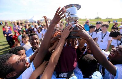 The players from IRCOM, The Immigrant and Refugee Community Organization of Manitoba Inc. soccer team, hoist their trophy as the players from St. John's Ravenscourt look on, following the final game of the boys under-13 city recreation final at John Blumberg, Saturday.