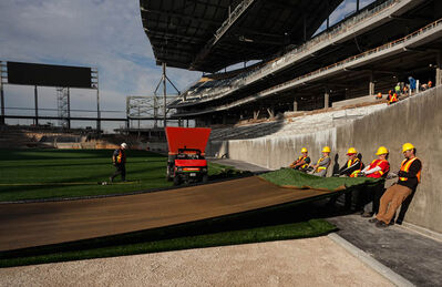 Workers tug on one of the final pieces of artifical turf installed at Investors Group Field on Tuesday.