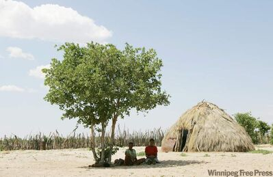 Two Basarwa women hide from the scorching sun in Metsiamenong, a remote village in the heart of the Central Kalahari Game Reserve, Botswana.