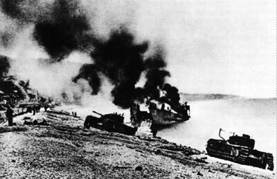 British Churchill tanks and landing craft burning on the Dieppe beach.