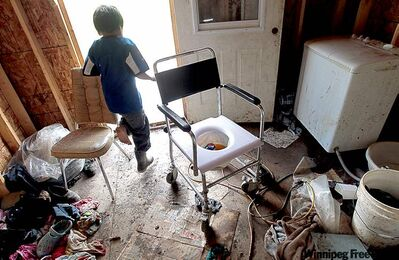 A child runs past a makeshift toilet in a house in Garden Hill First Nation.