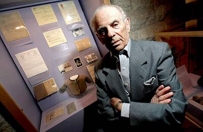 Joe Riesenbach in front of exhibit that tells his story and those of other Holocaust survivors.