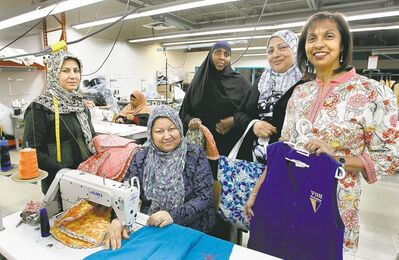 Institute president Yasmin Ali (right), outreach and program co-ordinator Ahlam Jasim (second from right), with sewing trainees Habiba Liben, Fetemeh Feizi (at sewing machine), Soheilla Karimi and Asha Mohamed (back).