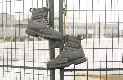 A pair of work boots hang on the security fence outside London, Ont., locomotive-builder Electro-Motive early this year. The plant was closed and moved to Indiana. Canadian labour relations are expected to face another rocky year in 2013.