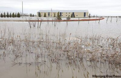 A building is surrounded by waters covering a field in St. Francois Xavier Friday.