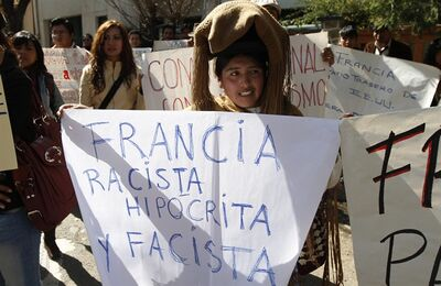 "A demonstrator holds a sign that reads in Spanish: ""France; Racist, hypocrite and fascist,"" outside the French embassy during a protest over France's alleged refusal to let the Bolivian president's plane cross over French airspace, in La Paz, Bolivia, Wednesday, July 3, 2013. Bolivia's Foreign Minister David Choquehuanca says the plane bringing President Evo Morales home from Russia was rerouted to Austria after France and Portugal refused to let it to cross their airspace because of suspicions that NSA leaker Edward Snowden was on board. (AP Photo/Juan Karita)"