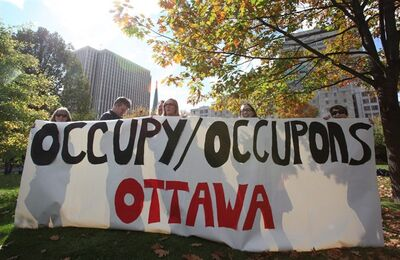 "Protesters hold a sign at the ""Occupy Ottawa"" protest at Confederation Park in Ottawa on Saturday, Oct. 15, 2011. The Mounties compiled a dossier on the Occupy Ottawa movement, scouring social media sites and even quizzing campus security after protesters held planning sessions at a university, newly released documents show.THE CANADIAN PRESS/Patrick Doyle"