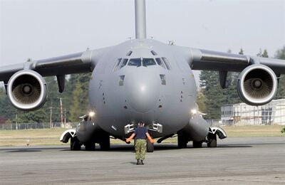 An official guides a C-17 Globemaster III into position after landing at the Abbotsford International Airport, in Abbotsford, B.C., Saturday, August 11, 2007. Canada is contributing one of its large C-17 military cargo planes to deliver supplies to the capital of Mali after a request from France. THE CANADIAN PRESS/Richard Lam