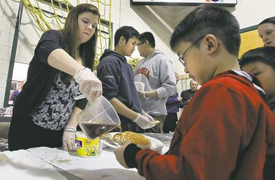 WAYNE GLOWACKI/ WINNIPEG FREE PRESS St. James Collegiate student Sierra Betker pours syrup on pancakes belonging to Reagan Banzon,  a Grade 1 student at Brooklands School, during the annual breakfast and literacy project Thursday.