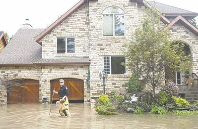 A Calgary firefighter checks on a flooded home.