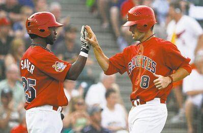Nick Liles (8) high-fives teammate Ray Sadler as he crosses the plate during the second inning Friday.