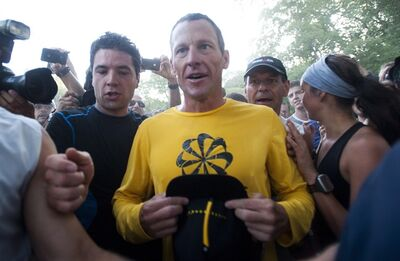 Lance Armstrong is swamped by supporters following a run in Mont Royal Park in Montreal, Wednesday, August 29, 2012. THE CANADIAN PRESS/Graham Hughes