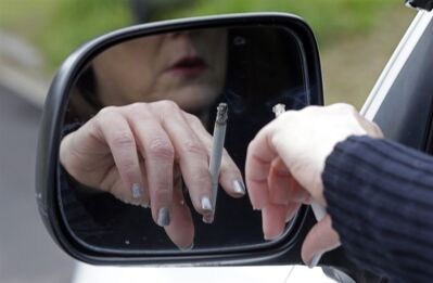 In this Saturday, March 2, 2013 photo, a woman smokes a cigarette while sitting in her truck in Hayneville, Ala. A new study released on Monday, March 4, 2013 offers more compelling evidence that life expectancy for some U.S. women is actually falling. A new study found that over 10 years, death rates for women under age 75 increased in nearly half of U.S. counties - many of them rural and in the South and West. There was no such trend among men. Some leading theories blame higher smoking rates and higher unemployment, but several experts said they simply don't know. (AP Photo/Dave Martin)