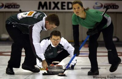 "PEI Skip Robert Campbell pushes his rock against Quebec Monday afternoon in Morris at the ""Canadian Mixed. Sweepers are Robbie Doherty (left) and lead Jackie Ried."