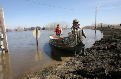 Ray Shaw (front) and Barry Penner pull their boats ashore onto the Morris ring dike next to Highway 75.