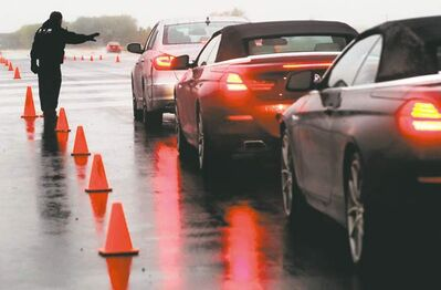 Track in the rain: Track controller Bob Armstrong manages traffic at the test drive track last year at the Automobile Journalists Association of Canada's TestFest Canadian Car of the Year Awards in Niagara-on-the-Lake, Ont. This year, 60 new entries will be evaluated.