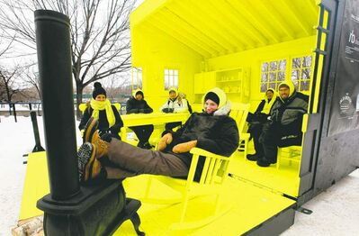 Landscape architect Liz Wreford-Taylor (front) and her Hygge House co-creators relax Thursday in their brilliant-yellow warming hut on the river. The local design took first place in this year's competition.
