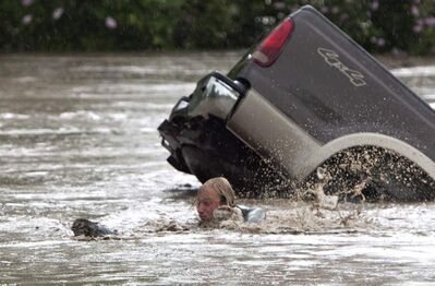 Kevan Yaets swims after his cat Momo to safety in High River, Alta. on Thursday after his truck was swept away.
