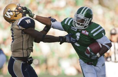 Saskatchewan Roughriders running back Kory Sheets runs the ball past Winnipeg Blue Bombers defensive back Brandon Stewart during the second half of CFL football action in Regina, Sask., Sunday, September 02, 2012. The Riders defeat the Bombers 52-0.